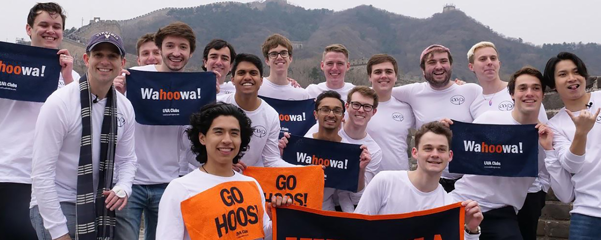 "UVA A Capella Group holding ""Wahoowa!"" and ""Go Hoos'"" signs"